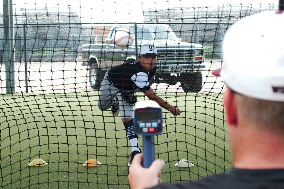 Clear Creek baseball coach Brandon Muller uses a radar gun to measure the speed as J.J. Hawthorn participates in a throwing speed challenge at the Clear Creek summer baseball camp. Photo: Kirk Sides / Houston Chronicle / © 2018 Kirk Sides / Houston Chronicle