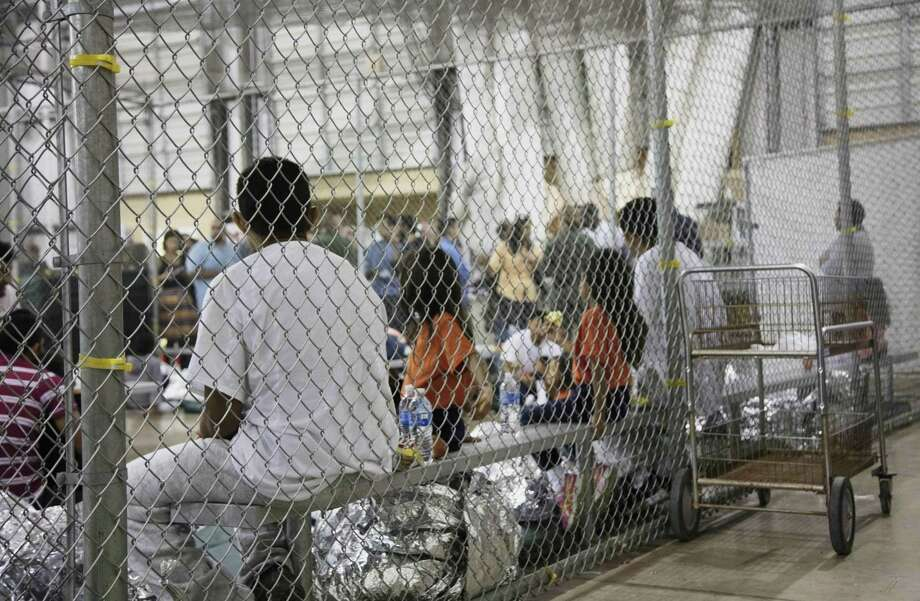 In this photo provided by U.S. Customs and Border Protection, people who've been taken into custody related to cases of illegal entry into the United States, sit in one of the cages at a facility in McAllen. Photo: Associated Press / U.S. Customs and Border Protection's Rio Grande Valley Sector