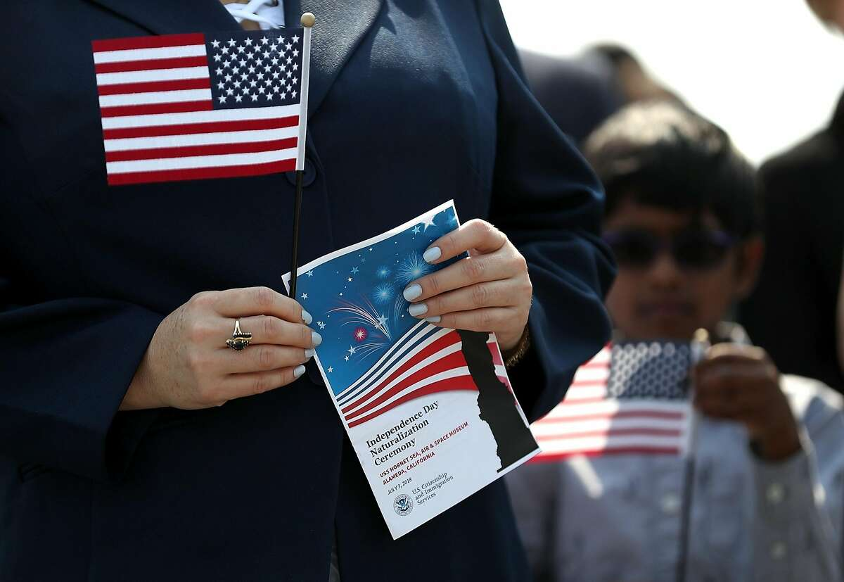FILE-- An immigrant holds an American flag before being sworn in as an American citizen during a naturalization ceremony on the flight deck of the USS Hornet on July 3, 2018 in Alameda. A federal judge upheld the core of California's sanctuary laws Thursday, rejecting a Trump administration lawsuit that argued the state was violating U.S. law by restricting local cooperation with federal immigration agents.