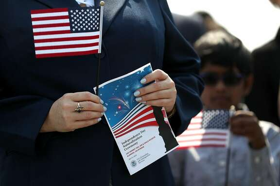 ALAMEDA, CA - JULY 03:  An immigrant holds an American flag before being sworn in as an American citizen during a naturalization ceremony on the flight deck of the USS Hornet on July 3, 2018 in Alameda, California. 76 immigrants from 31 countries were sworn in as American  citizens during a ceremony aboard the historic USS Hornet aircraft carrier.  (Photo by Justin Sullivan/Getty Images)