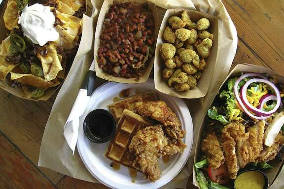 A roundup of food from Hoppin' John, a Southern-style restaurant at The Vistana. Clockwise from top left: brisket nachos, hoppin' John, fried okra, chicken and waffles and a hot chicken salad. For Mike Sutter's review