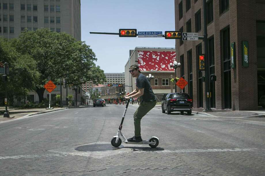 Marty Lind of Austin crosses Commerce Street in downtown San Antonio on an electric Bird scooter recently. Electric scooters are a lot like the foot-powered playthings most of us rode as a kid, only better. Two or three foot kicks engages the motor and balancing is easy — if you can ride a bicycle, you can ride a scooter. Photo: Josie Norris /San Antonio Express-News / © San Antonio Express-News