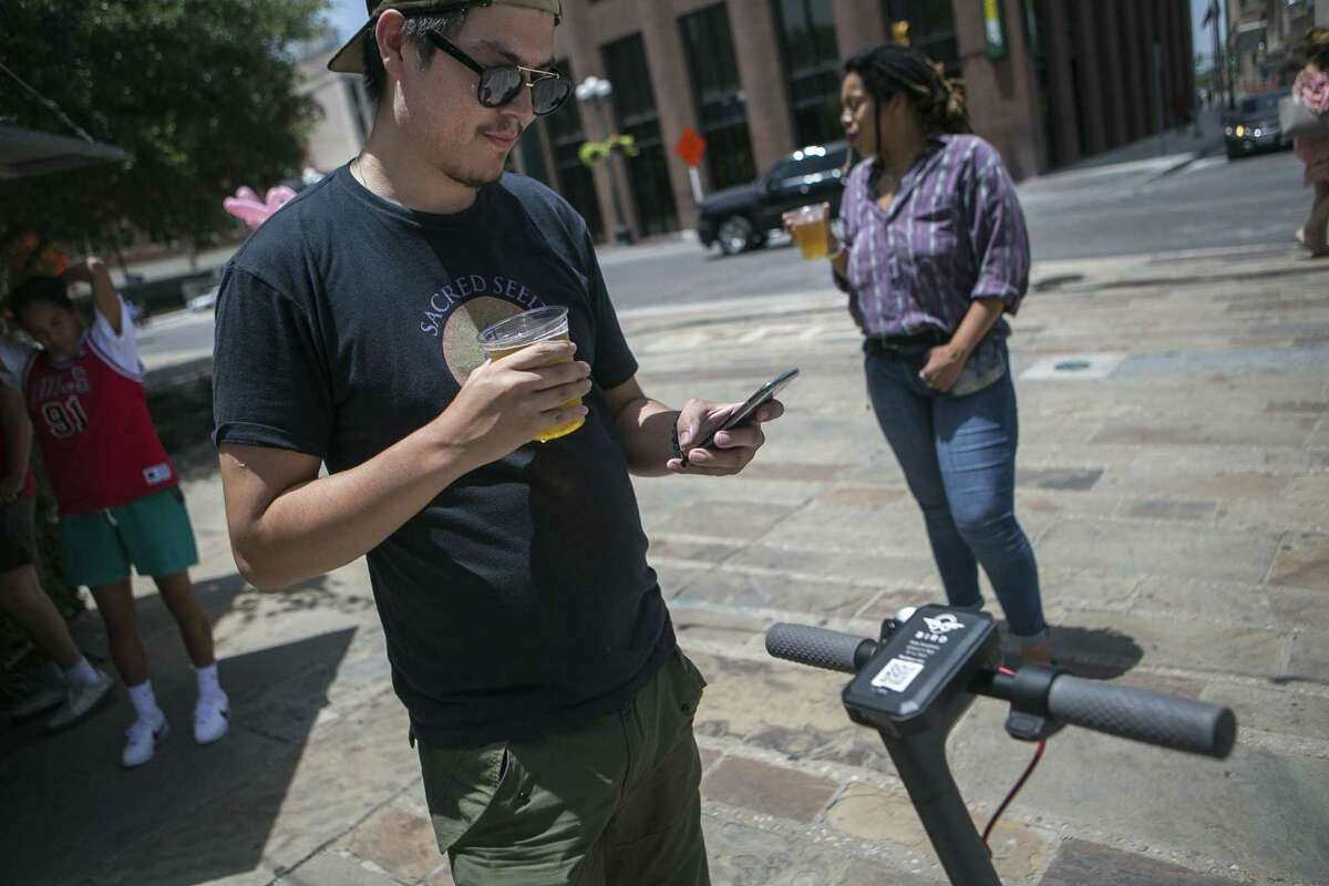 Marty Lind of Austin turns off an electric Bird scooter by using his phone in downtown San Antonio July 1, 2018. There are around 150 Bird electric scooters deployed downtown, in Dignowitty Hill, Government Hill and Southtown. Anyone can use them by downloading the Bird app and paying $1 plus $0.15 per minute. The city didn't know about the recent deployment of the devices, which can be left anywhere, but is working quickly to develop regulations.