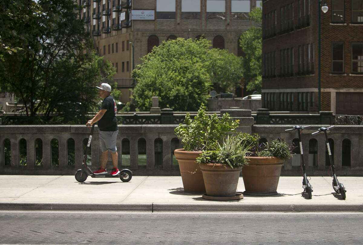A man rides am electric Bird scooter in downtown San Antonio July 1, 2018. There are around 150 Bird electric scooters deployed downtown, in Dignowitty Hill, Government Hill and Southtown. Anyone can use them by downloading the Bird app and paying $1 plus $0.15 per minute. The city didn't know about the recent deployment of the devices, which can be left anywhere, but is working quickly to develop regulations.