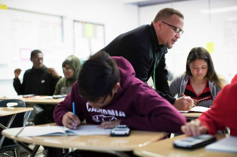 Houston ISD's Worthing High School math teacher Michael Judge helps Hilda Martinez, 15, a newcomer from Honduras with math problems during the Algebra I class in Houston. Photo: Marie D. De Jesús / © 2018 Houston Chronicle