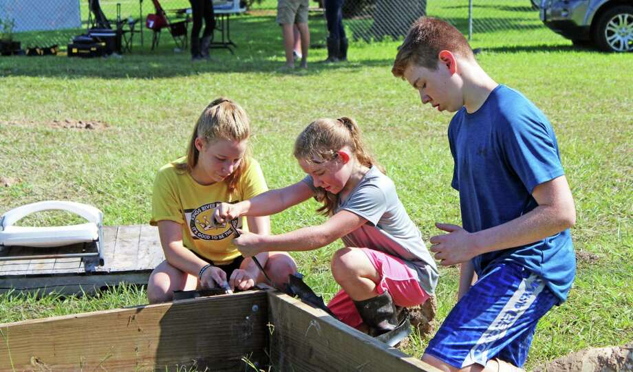 Brielle Alder (left) and Brynlee Alder (right) help their brother Dallen Alder construct a vegetation box in front of Lake Houston in Huffman. Photo: Kaila Contreras