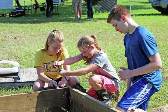 Brielle Alder (left) and Brynlee Alder (right) help their brother Dallen Alder construct a vegetation box in front of Lake Houston in Huffman.