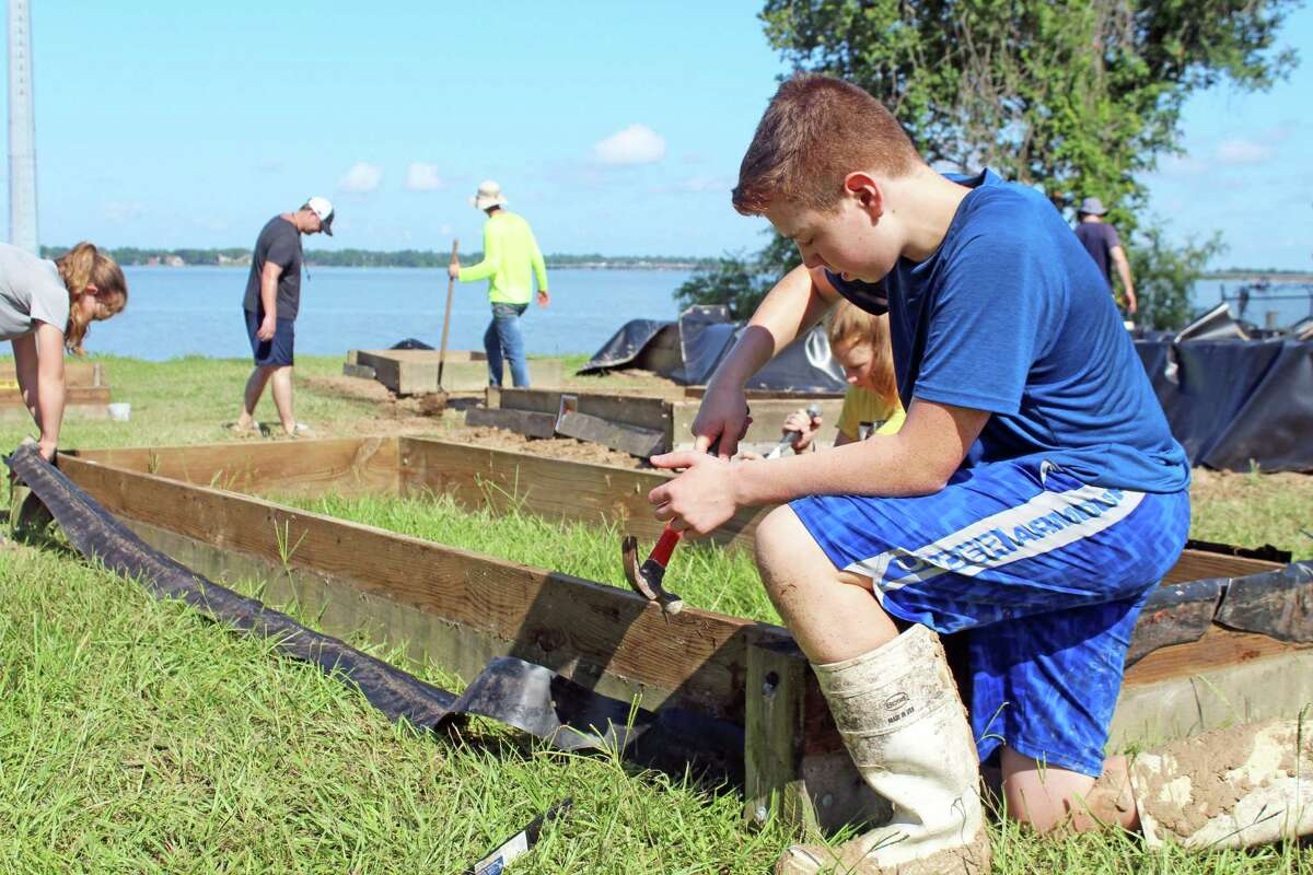 Huffman resident Dallen Alder constructs a vegetaion box for plants in front of Lake Houston to improve the flora and fauna of the area.
