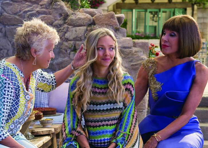 """Amanda Seyfried's Sophie (center) is taking on grownup responsibilities in the musical sequel, """"Mamma Mia! Here We Go Again."""" Luckily, she has her mom's best friends, Rosie (Julie Walters) and Tanya (Christine Baranski) to help her through.   (L to R) Rosie (JULIE WALTERS), Sophie (AMANDA SEYFRIED) and Tanya (CHRISTINE BARANSKI) in """"Mamma Mia! Here We Go Again.""""  Ten years after """"Mamma Mia! The Movie,"""" you are invited to return to the magical Greek island of Kalokairi in an all-new original musical based on the songs of ABBA."""
