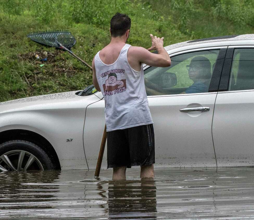 Dan Gorman give an indication of how much the water has receded at the intersection of N. Pine St and Lancaster while a woman stranded in a car waits for a tow truck. Thursday July 5, 2018 in Albany, N.Y. (Skip Dickstein/Times Union)