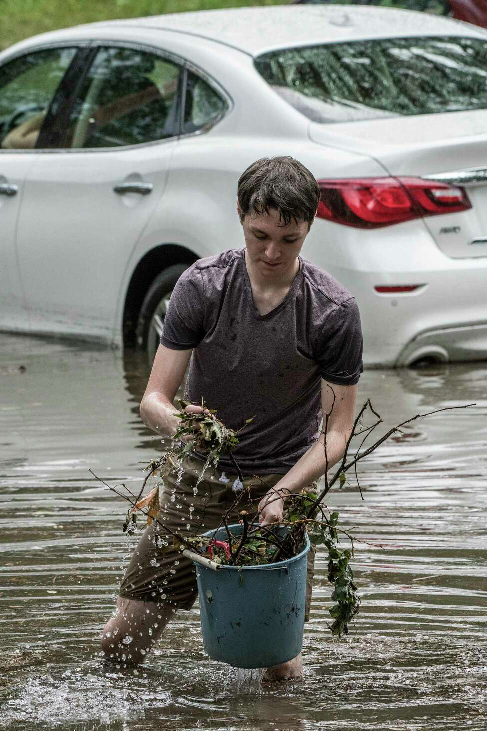 Justin Jasiewicz, 19, voluntarily clears obstructions from the sewer drains at the intersection of N. Pine St and Lancaster while a woman stranded in a car waits for a tow truck. Thursday July 5, 2018 in Albany, N.Y. (Skip Dickstein/Times Union)