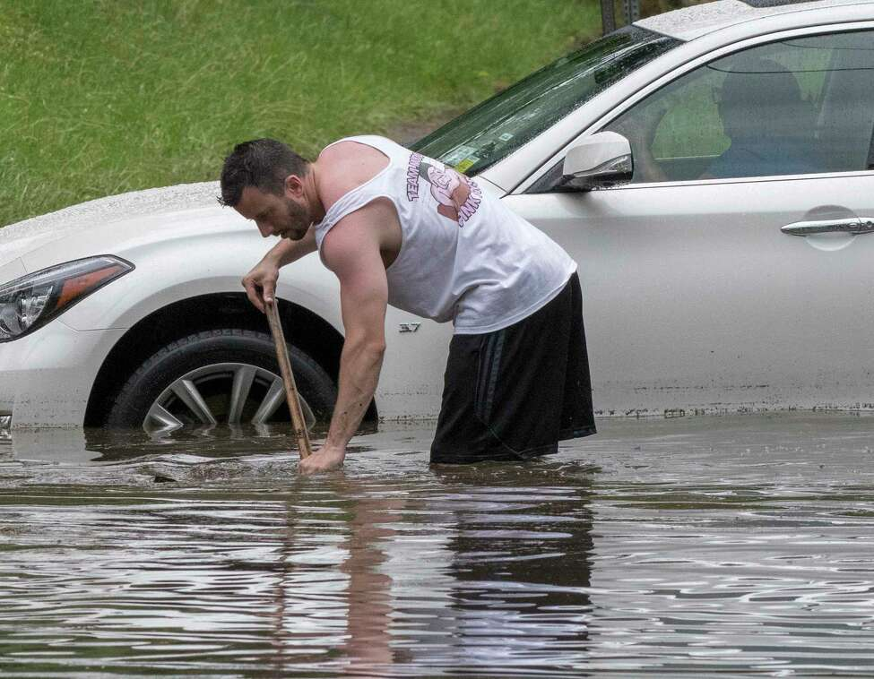 Dan Gorman voluntarily clears obstructions from the sewer drains at the intersection of N. Pine St and Lancaster while a woman stranded in a car waits for a tow truck. Thursday July 5, 2018 in Albany, N.Y. (Skip Dickstein/Times Union)