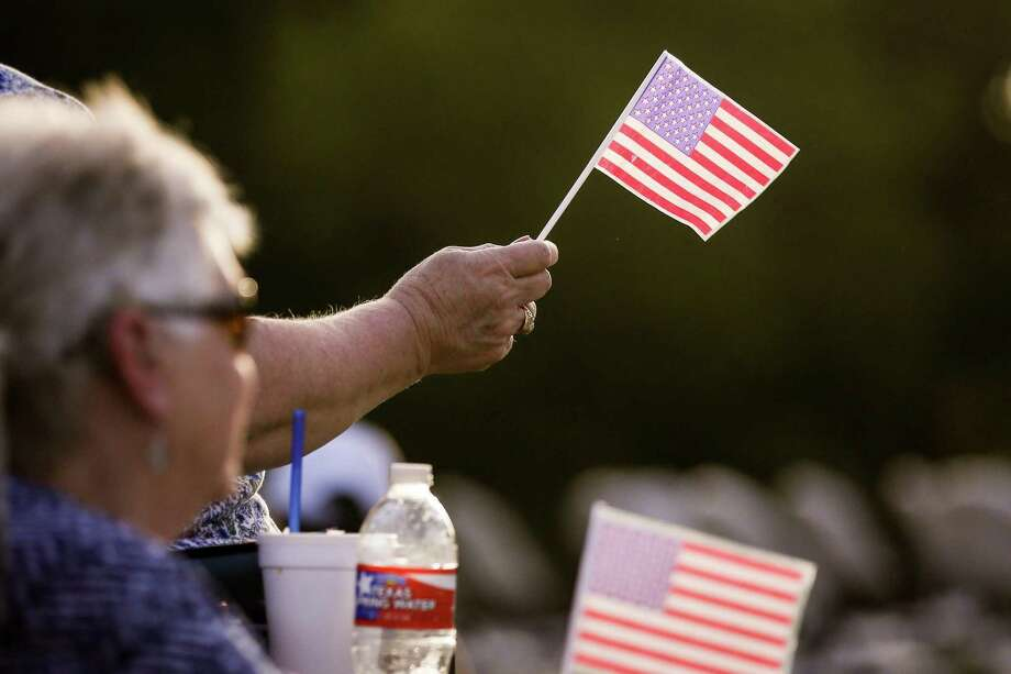 Audience members wave U.S. flags during the Conroe Symphony Orchestra's Patriotic Celebration performance on Saturday, June 30, 2018, at Heritage Place Park. Photo: Michael Minasi, Staff Photographer / Houston Chronicle / © 2018 Houston Chronicle