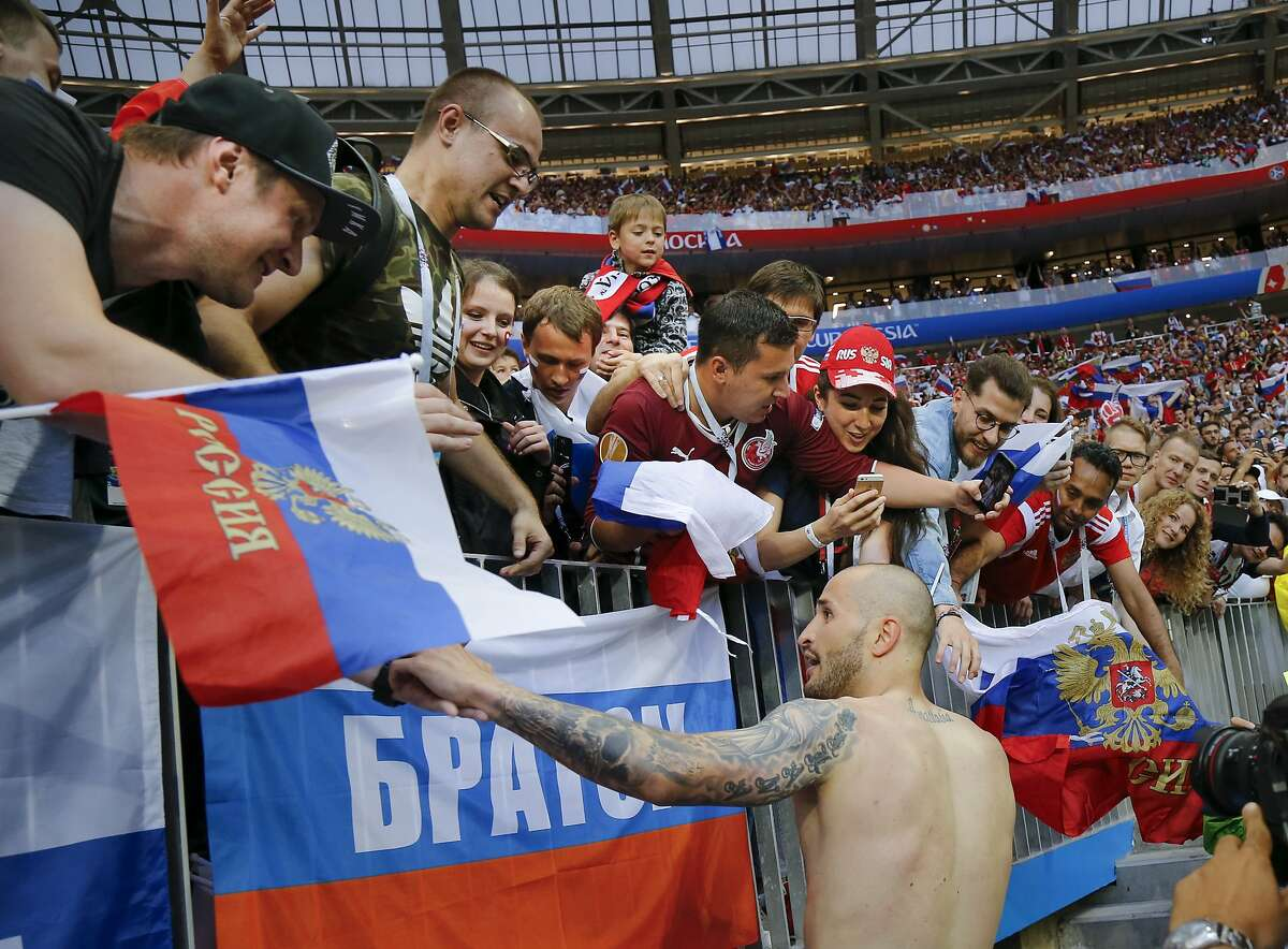 Russia's Fyodor Kudryashov, bottom, celebrates with fans after winning the round of 16 match between Spain and Russia at the 2018 soccer World Cup at the Luzhniki Stadium in Moscow, Russia, Sunday, July 1, 2018. Russia shocks Spain at the World Cup, beating the 2010 champion 4-3 in a penalty shootout after a 1-1 draw. (AP Photo/Alexander Zemlianichenko)