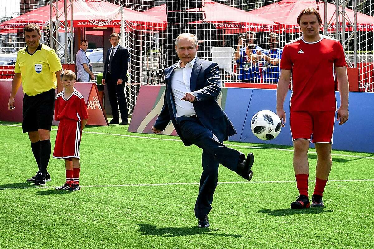 TOPSHOT - Russia's President Vladimir Putin (C) kicks a ball as he takes part in the opening of an exhibition soccer match at the World Cup Football Park on the Red Square in Moscow on June 28, 2018. / AFP PHOTO / Yuri KADOBNOVYURI KADOBNOV/AFP/Getty Images