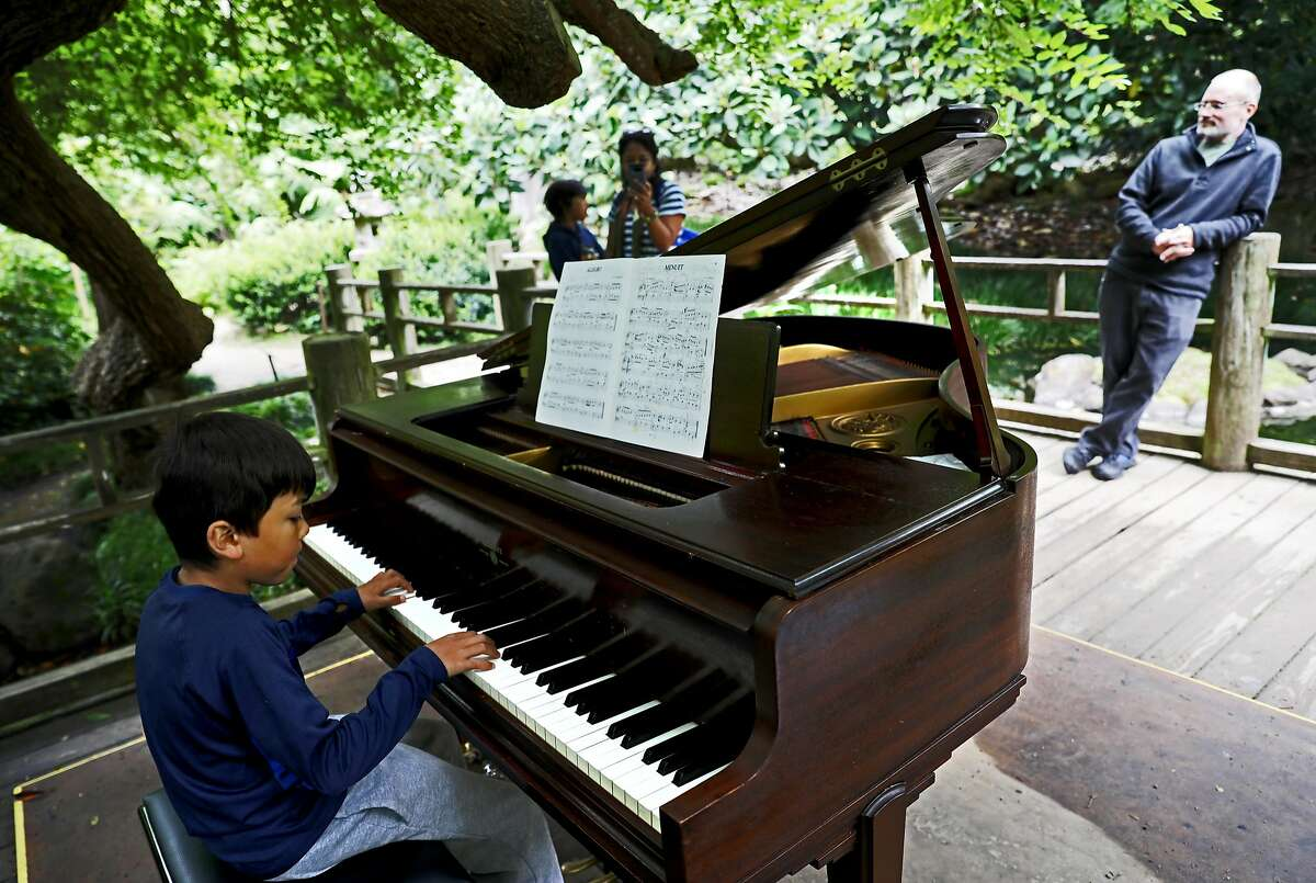 Julien Poncin, 8, performs Menuet by Johann Sebastian Bach in the Moon Viewing Garden at the San Francisco Botanic Garden in San Francisco, California on Thursday, July 5, 2018. A dozen pianos are currently scattered around the grounds as part of the annual Flower Piano event running from now through July 16.