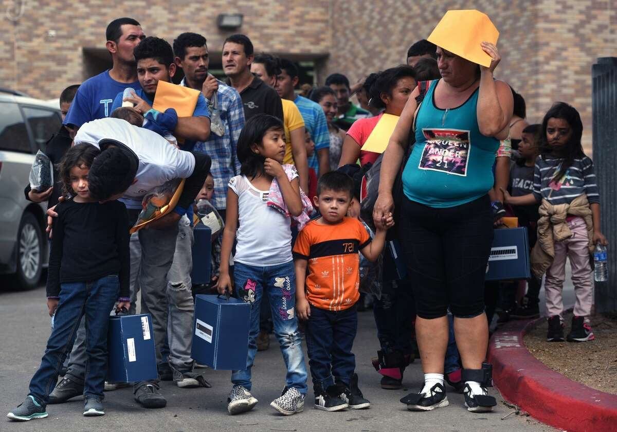 June 29, 2018 - McAllen, Texas - Newly released immigrants dropped off at Central bus station are met by a volunteer and walk to Catholic Charities of the Rio Grande Valley (CCRGV) with the help of the Sacred Heart Church, the City of McAllen, which serves as a humanitarian respite center after immigrants are processed and released. They are given food, clothes, shoelaces which were taken from them, medical attention and welcoming warmth. Carol Guzy/ for San Antonio Express-News