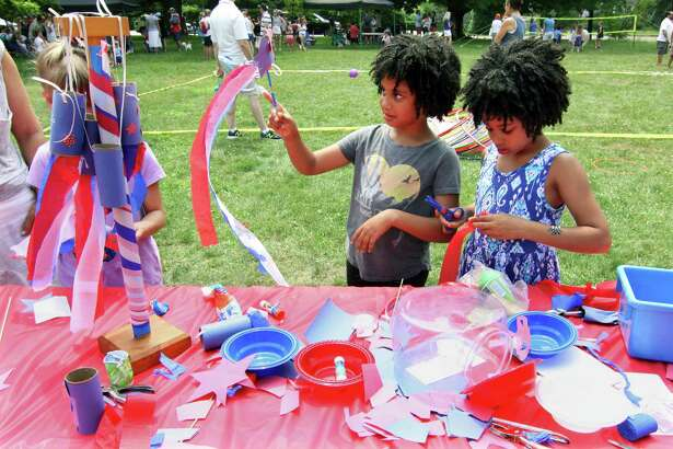 Twins Nnisa Gupta-Nwanze, 8, of Westport, and her sister Meera, right, create their own July 4th themed wind socks during the Pequot Library's annual 4th of July Bike Parade and Lawn Games event in Southport, Conn., on Wednesday July 4, 2018.