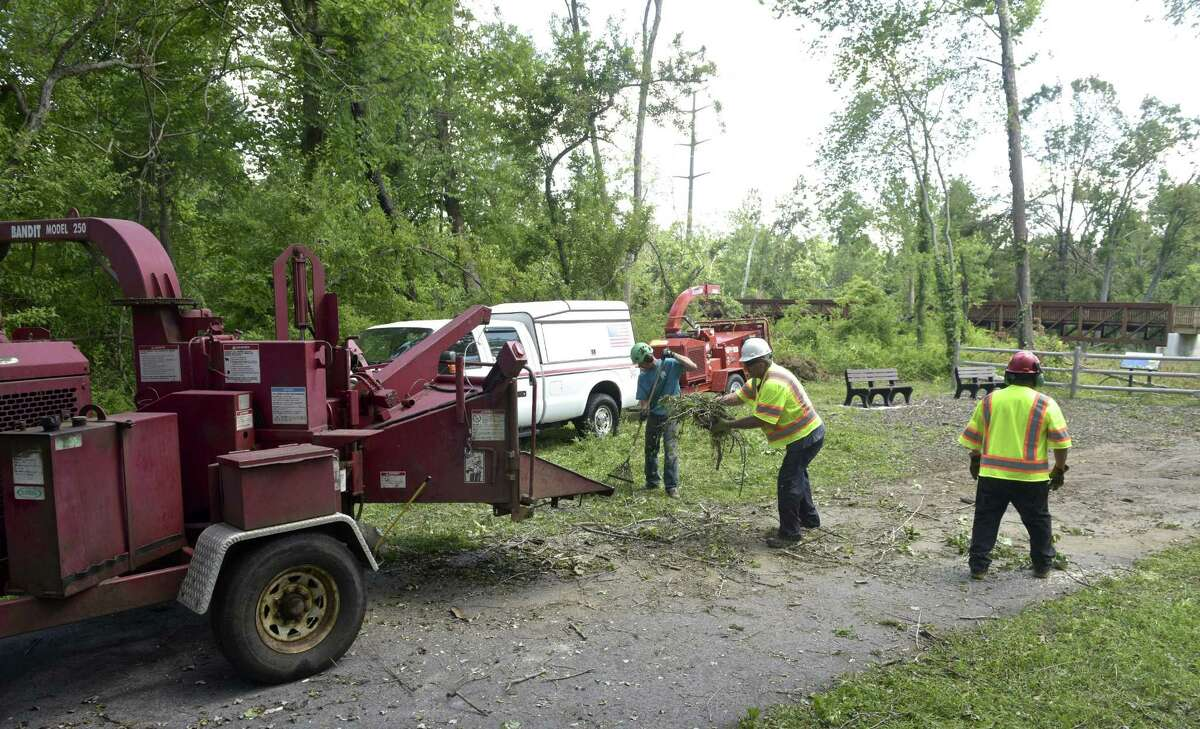 Mike Tatroe, center, Krisztian Mateisz, left, and Salvino Guerrero work on cleaning up the Still River Greenway. The trail has been closed since the May 15 storm that injured two people on the trail. Lewis Tree Service and Wright Tree Service are donating their time to clear the trail from the police station to downtown. Brookfield, Conn, Thursday, July 5, 2018.