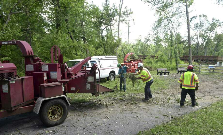 Mike Tatroe, center, Krisztian Mateisz, left, and Salvino Guerrero work on cleaning up the Still River Greenway. The trail has been closed since the May 15 storm that injured two people on the trail. Lewis Tree Service and Wright Tree Service are donating their time to clear the trail from the police station to downtown. Brookfield, Conn, Thursday, July 5, 2018. Photo: H John Voorhees III / Hearst Connecticut Media / The News-Times