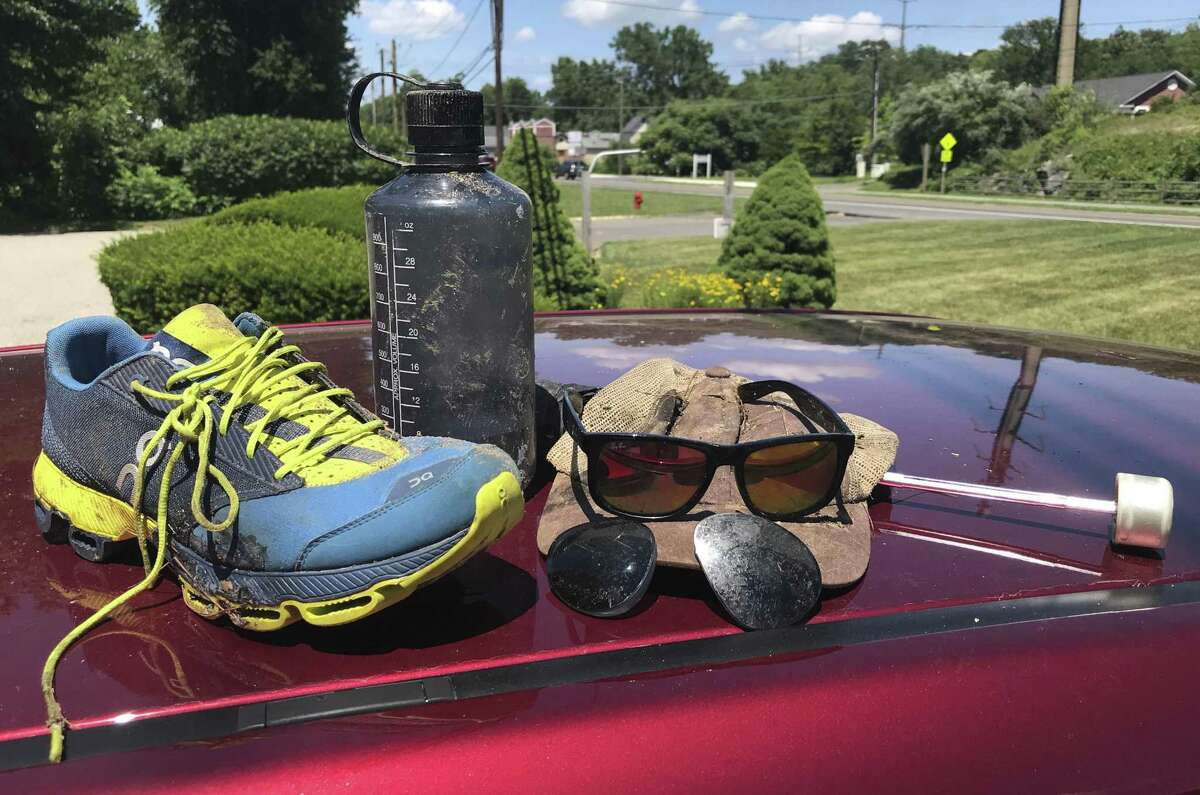Belongings of a Bethel women and a visiting relative who were injured in the May 15 storm on the Still River Greenway were recovered this week by workers from local firms who began cleaning up the trail this week. The trail has been closed since the storm. Thursday, July 5, 2018, in Brookfield, Conn. Lewis Tree Service and Wright Tree Service are donating their time to clear the trail from the police station to downtown.