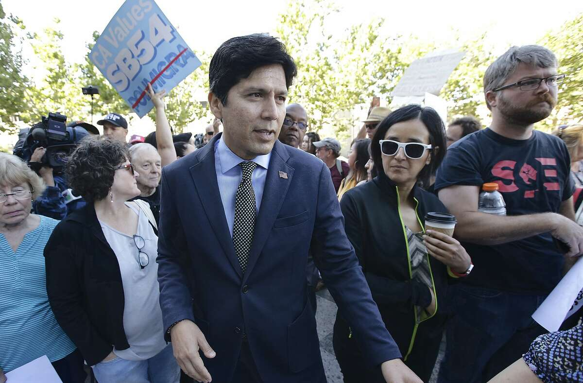 State Sen. Kevin de Leon, D-Los Angeles, makes his way through the crowd outside the federal courthouse where a federal judge will hear arguments over the U.S. Justice Department's request to block three California laws that extend protections to people in the country illegally, Wednesday, June 20, 2018, in Sacramento, Calif. De Leon authored SB54, one of the laws before the court. (AP Photo/Rich Pedroncelli)