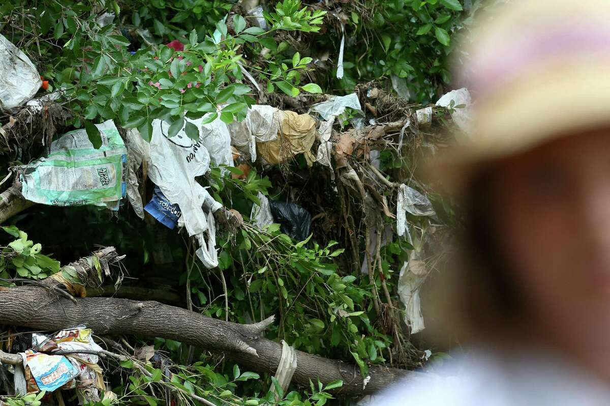 Plastic bans can be seen on the foliage of Woodland Park, where Zero Waste Houston volunteers talked to reporters about the Texas Supreme Court ruling against the local ordinances on single-use plastic bans June 22.