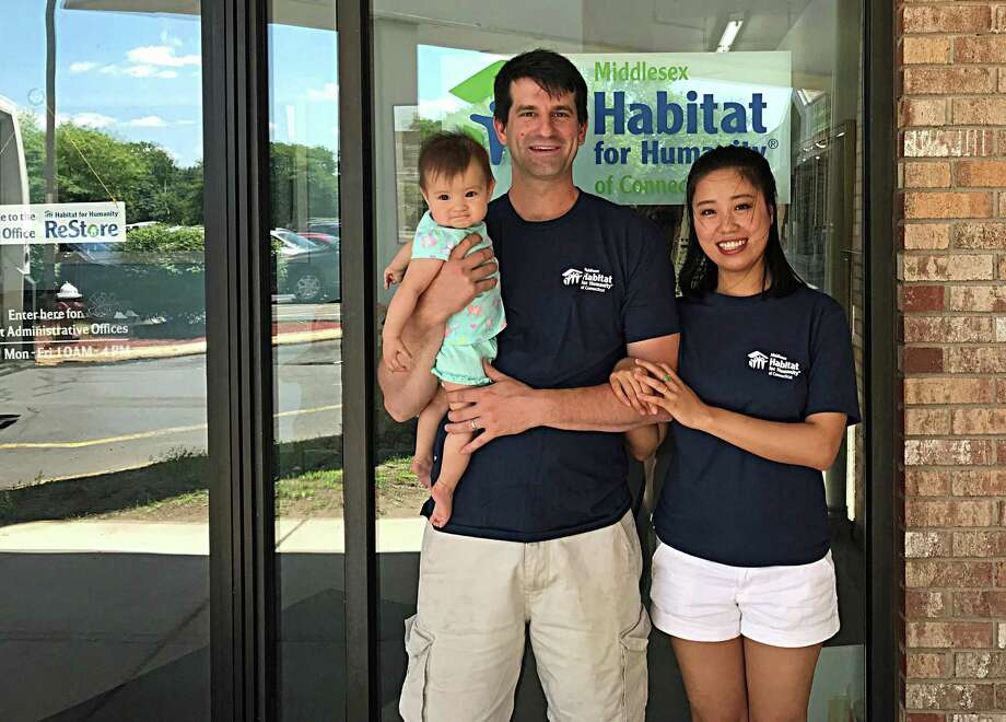 Glastonbury-based architect firm, The S/L/A/M Collaborative organized 18 employees during a recent Middlesex Habitat for Humanity of Connecticut build day. Shown are future homeowners, from left, Marine Dustin Fitzpatrick, his wife Yiran and their daughter Sophia, who expect to move in to their Portland home next April. Photo: Contributed Photo