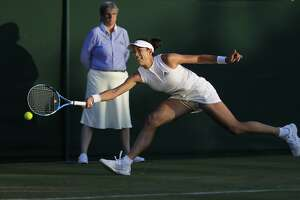 Spain's Garbine Muguruza returns the ball to Alison Van Uytvanck of Belgium, during their women's singles match, on the fourth day at the Wimbledon Tennis Championships in London, Thursday July 5, 2018. (AP Photo/Ben Curtis)