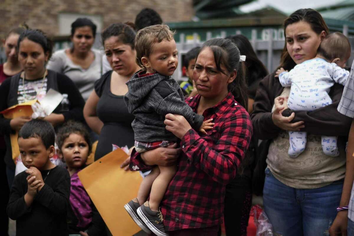 MCALLEN, TEXAS - June20, 2018: Asylum seeker Apolinaria, 37, center, who did not want to use her last name, holds her two-year-old son while waiting to be escorted to the Catholic Charities Humanitarian Respite center before making her final trip to stay with family members. She lost her house during the volcano eruption in Guatemala.
