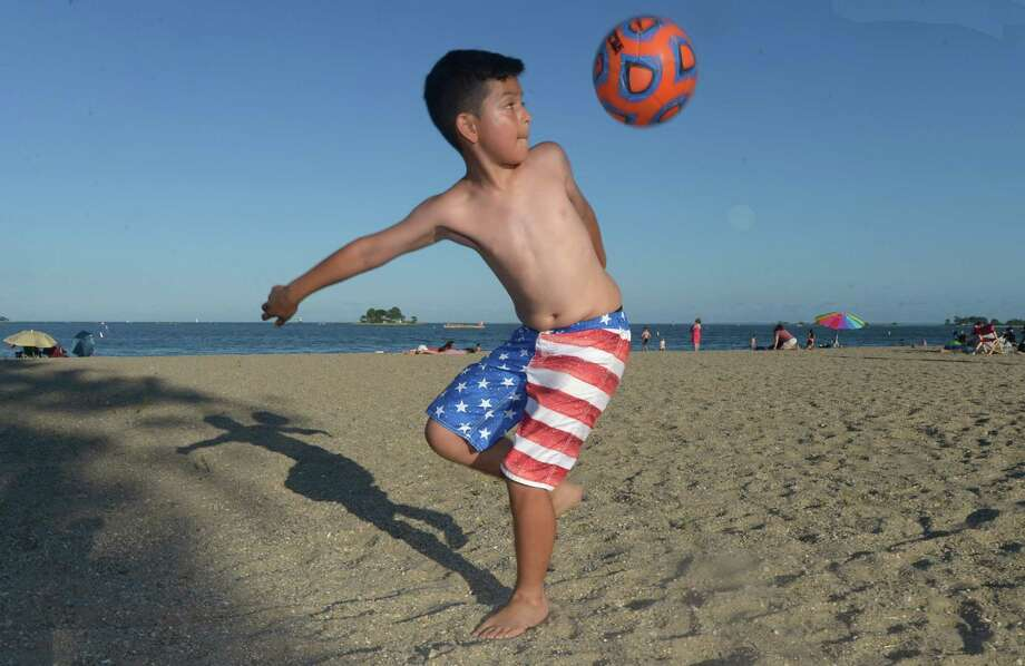 Norwalk resident Chrsistopher Patino flips his soccer ball as he awaits the fireworks display during an evening at Calf Pasture Beach Thursday, July 5, 2018, in Norwalk, Conn. Photo: Erik Trautmann / Hearst Connecticut Media / Norwalk Hour
