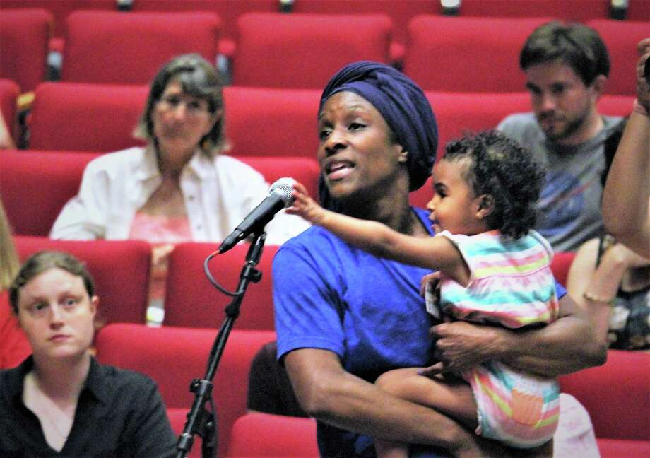 At a town hall meeting held by Sen. Chris Murphy at the University of Hartford, Aaliyah Miller of East Hartford asked a question about tariffs -- wouldn't the people in red states be hurt by them and vote accordingly?  She's holding her 23-month-old daughter, Akilah Hadjsalem. Photo: Dan Haar / Hearst Connecticut Media