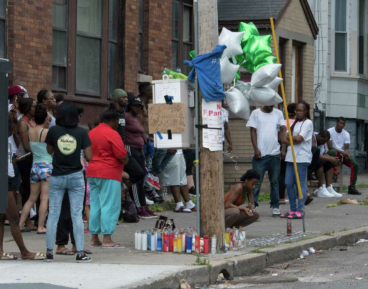 Mourners gather at a makeshift memorial at the corner of Orange and Lark Streets not far from the murder scene at 297 Orange Street to remember a fallen friend Thursday July 5, 2018 in Albany, N.Y. Four more people were shot early morning July 8, marking 11 shootings in a week. (Skip Dickstein/Times Union)