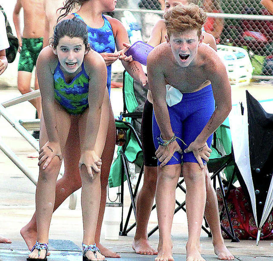 Summers Port's Grace Burris, left, and Austin Norton cheer on a teammate during Thursday night's SWISA dual meet in Godfrey against Splash City. Photo:       Pete Hayes | The Telegraph