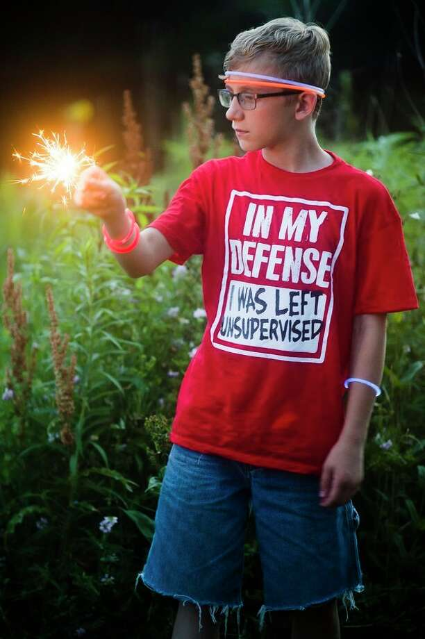 Xander Ullery of Midland, 12, lights a sparkler as thousands of people gather outside of Dow Diamond in Midland to watch fireworks on July 4, 2018. (Katy Kildee/kkildee@mdn.net)