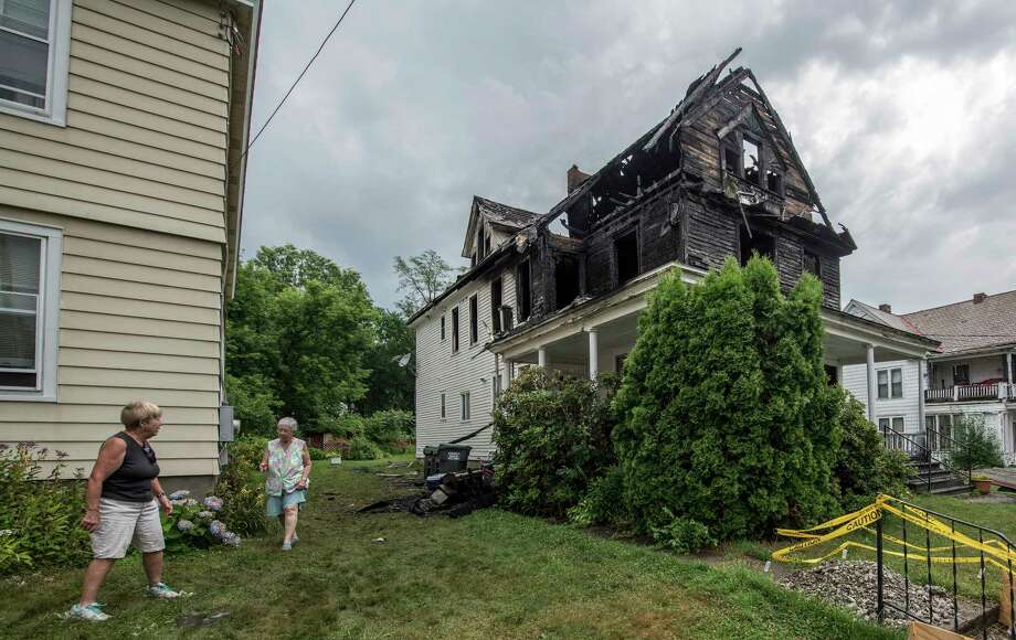 Neighbors look over at a multi-family dwelling which was destroyed during an early morning fire at 12 Fairview Avenue Friday July 6, 2018 in Waterford, N.Y. (Skip Dickstein/Times Union) Photo: SKIP DICKSTEIN, Albany Times Union / 20044274A