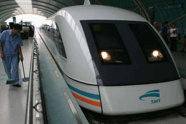 SHANGHAI, CHINA - JUNE 7:  (CHINA OUT; PHOTOCOME OUT)  A worker cleans the platform beside a Maglev train, also known as the magnetic levitation train at a station on June 7, 2005 in Shanghai, China. Shanghai boasts the world's only commercial high-speed railway supported by maglev technology. The rail line,  developed by Germany's Transrapid International Consortium, takes eight minutes to hurtle the 30 kilometres from Shanghai airport to the city's outskirts, a journey which takes up to an hour by car. A magnetic charge lifts the train's sleek carriages, first of their kind in the world, one centimetre above the track. The train's top speed is 430 kilometres per hour. The Maglev line has impressed British Chancellor of the Exchequer Gordon Brown as he rode the train in February this year. British Prime Minister Tony Blair has held a seminar to consider building a Maglev route along the spine of Britain through Birmingham, Manchester, Leeds, Newcastle and Edinburgh.