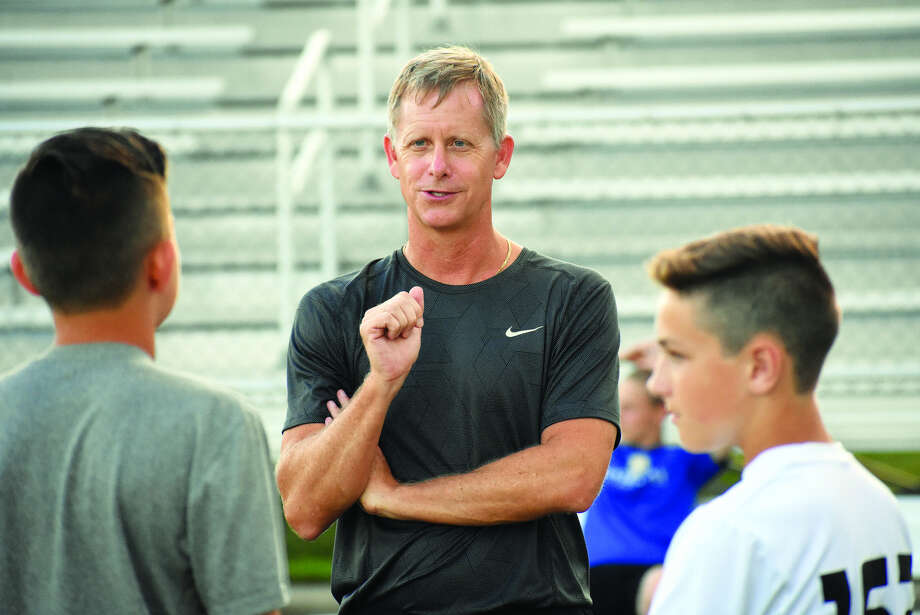 Edwardsville boys' soccer coach Mark Heiderscheid talks to two players before the start of a scrimmage on Thursday inside the District 7 Sports Complex.