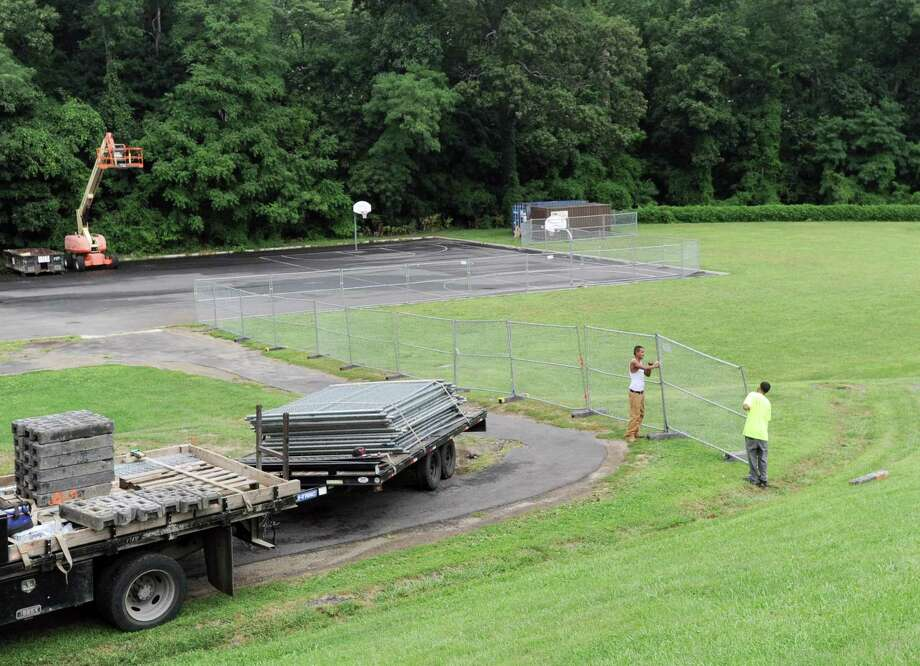 Workers install fencing around the fields at Western Middle School, Sept. 1, 2016. A portion of the fields reopened last year, but other parts remain closed off and more testing for contaminants will be conducted this summer. Photo: Bob Luckey Jr. / Hearst Connecticut Media / Greenwich Time