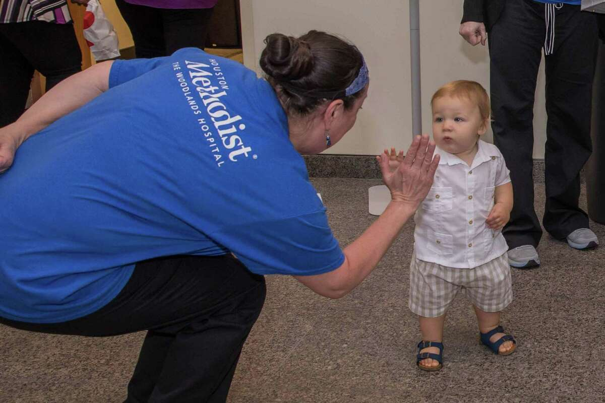 Houston Methodist The Woodlands' first baby, Jaxon Neal, offers a high-five to Hope Barbosa, one of the hospital's 1,000 employees, during a one-year celebration at Houston Methodist The Woodlands Hospital on June 26, 2018.