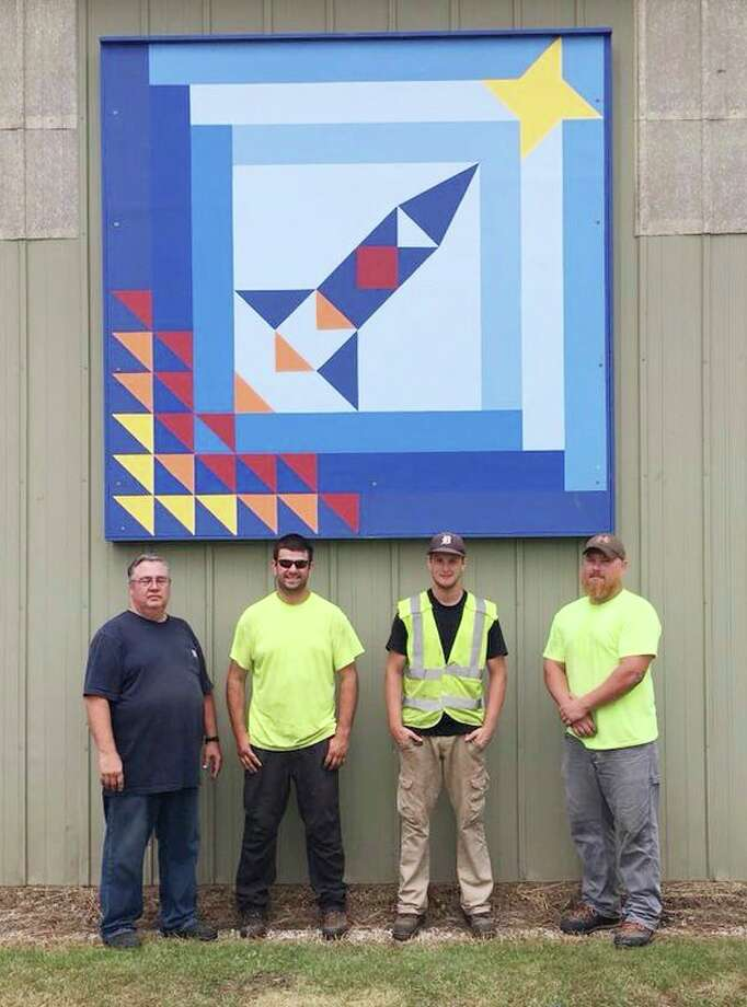 The 100th quilt block on the Thumb Quilt Trail was recently hung on Cass City's DPW building facing the park. Those who helped hang the block were Bob Frazer, Brady Kappen, Cody Orban and Jacob Ferrell. Cass City business Kappan Tree Service volunteers used a cherry-picker bucket and workers to mount the blocks. (Submitted Photo)