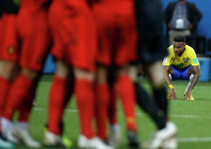 Brazil's Neymar looks to celebrating Belgian players after his team was eliminated in the quarterfinal match between Brazil and Belgium at the 2018 soccer World Cup in the Kazan Arena, in Kazan, Russia, Friday, July 6, 2018. (AP Photo/Francisco Seco)