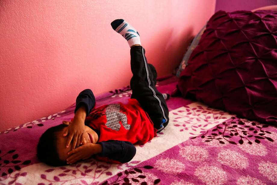 Jorgito covers his face for a picture. When someone he doesn't know arrives, he runs to the bedroom and hides, or lies on the ground clutching his stomach. Photo: Gabrielle Lurie / The Chronicle