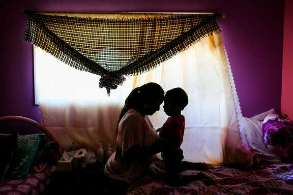 Jorgito, 5, and his cousin and caretaker Margarita (left) share a moment together in their bedroom after taking a portrait in San Mateo, California, on Thursday, July 5, 2018. Jorgito was separated from his mother at the Texas border and she was since deported back to Guatemala.