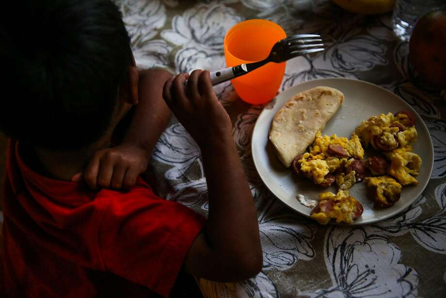 Jorgito eats dinner in the San Mateo County apartment of the cousin who took him in. The family is struggling financially, and some members are also undocumented immigrants. Photo: Gabrielle Lurie / The Chronicle
