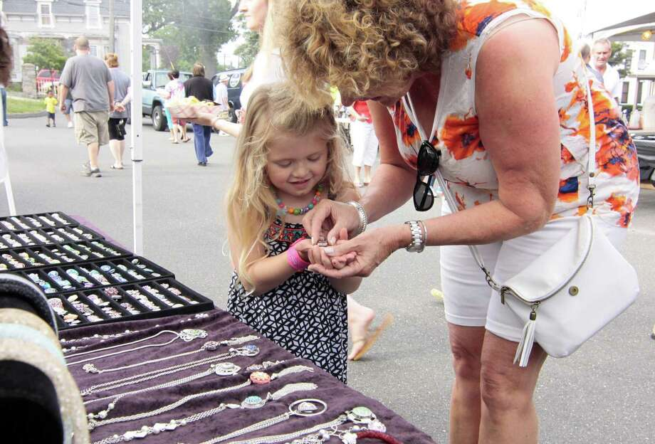 """Johanne Henderson, of Derby, helps her granddaughter Riley Shifflett, 4, pick out some jewelry from the """"Make-A-Bracelet"""" tent during St. Mary's Summer Festival held at St. Mary's Church grounds on Elizabeth Street in Derby, Conn., on Friday July 8, 2016. There is music played by DJ Megawatt along with food, crafts, a giant raffle and fun & games for the kids. Handicapped parking is behind the rectory. Photo: Christian Abraham / Hearst Connecticut Media / Connecticut Post"""