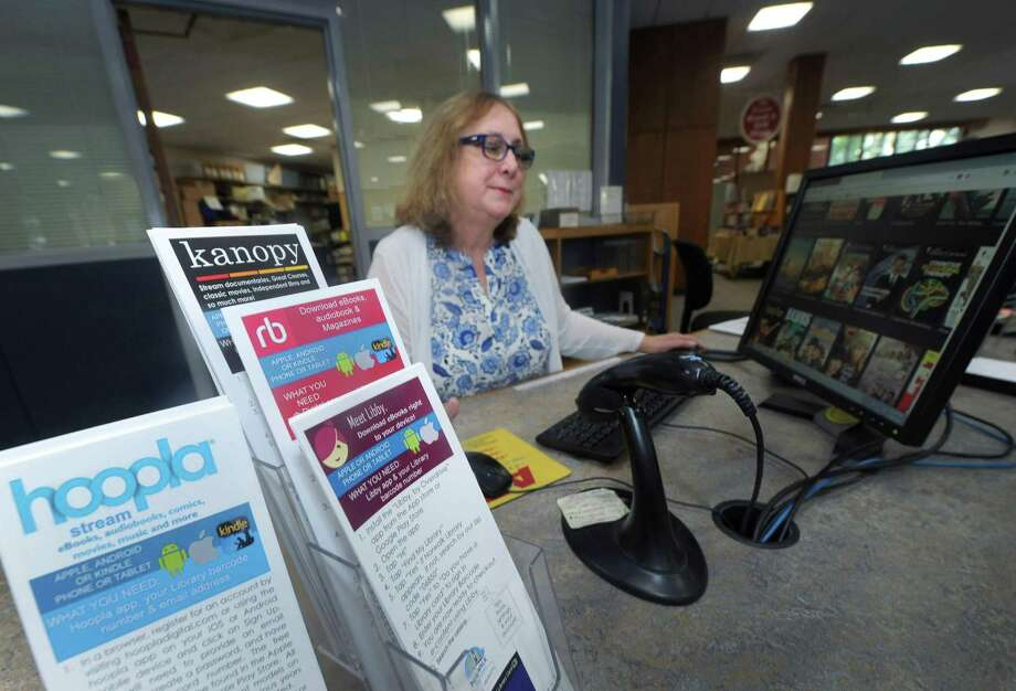 Cynde Lahey, Norwalk Public Library Director of Information Services, displays the digital databases and movie streaming services like Kanopy at the library Friday, July 5, 2018, in Norwalk, Conn. Kanopy which launched at the library in January and other digital resources at the library have seen a surge in use. Photo: Erik Trautmann / Hearst Connecticut Media / Norwalk Hour