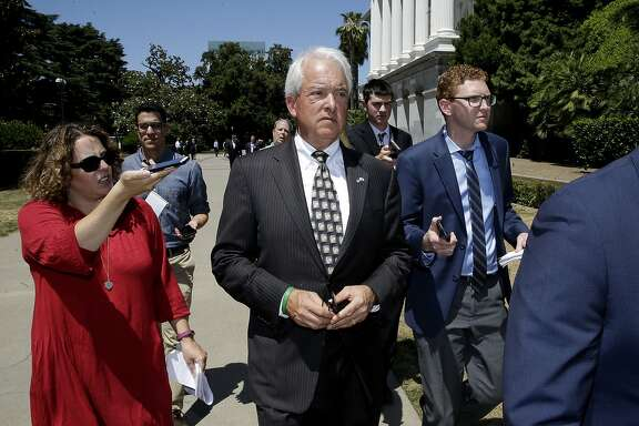 Republican gubernatorial candidate John Cox, center, is questioned by reporters as he leaves a news conference where he blasted a recent gas tax increase, Monday, June 18, 2018, in Sacramento, Calif. Cox is the chairman of a campaign to repeal the gas tax increase and faces Democratic Lt. Gov. Gavin Newsom in November. (AP Photo/Rich Pedroncelli)