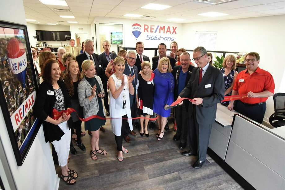 Ferdinando Bruno (holding scissors), the broker/owner of a RE/MAX office, celebrated a ribbon cutting June 27 at the new office, 800 Route 146 #120, Clifton Park. Bruno was joined by Sen. Jim Tedisco, town Supervisor Phil Barrett and real estate agents Faye Falvo Rispoli, Howard Rubinger and members of his team. (Photo provided) Photo: Mark Bolles / MarkBolles.com