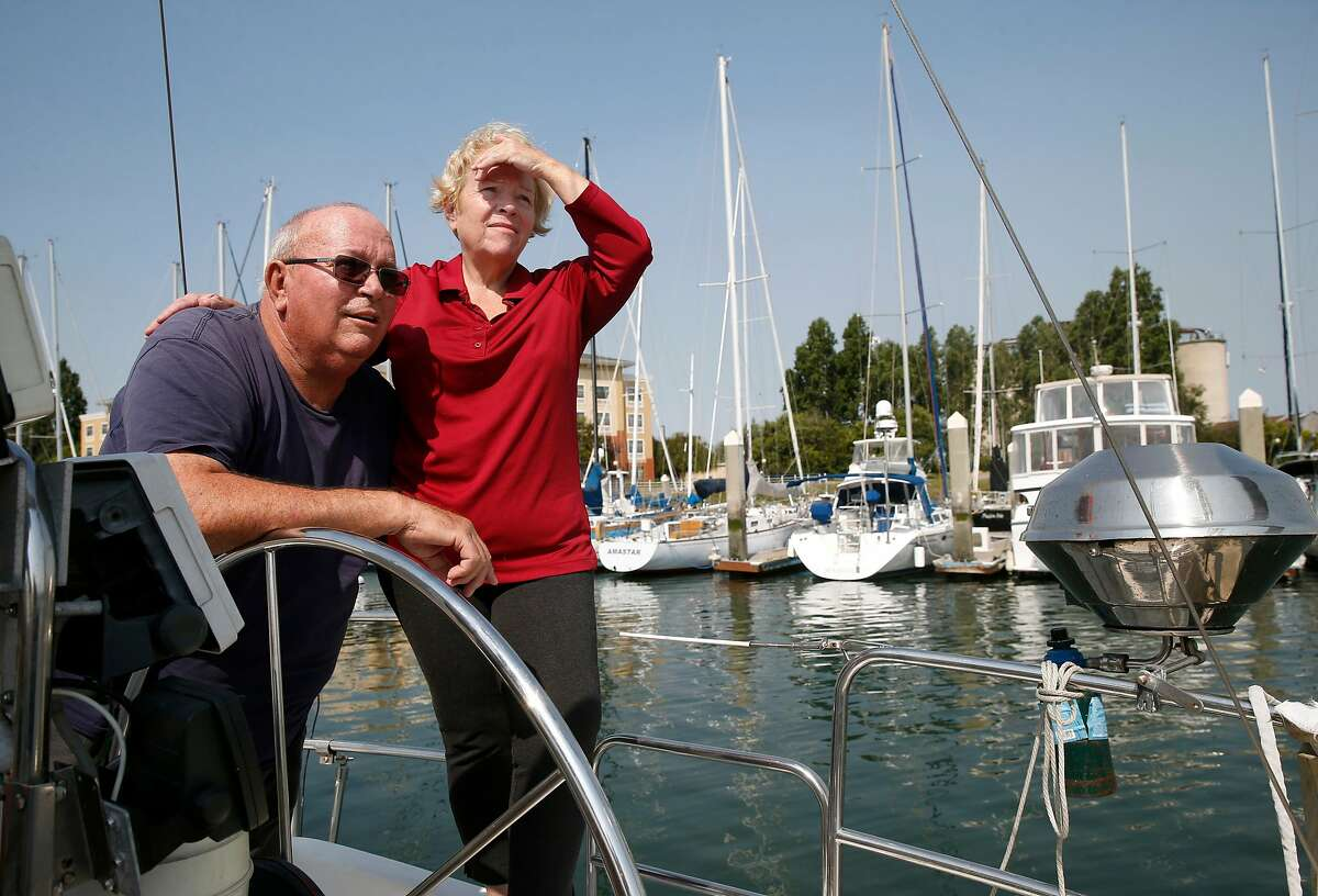Bill and Cathy Stapp stand on the deck of their sailboat Kruzin' Kitty in Alameda, Calif. on Tuesday, July 3, 2018. After being told they were eligible for the Covered California healthcare plan, the Stapp's were informed their combined income was too high to qualify for subsidized coverage and were ordered to reimburse the IRS several thousand dollars including penalty and interest.